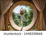 Small photo of Woman practising yoga (tree pose) in bamboo house studio. View of nature and mountains on background. Peaceful meditation spot. Ecolodge retreat, eco friendly house