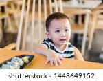 Small photo of Cranky asian child boy in restaurant.2.5 years old boy crying and sad.Mad kid got upset and sad and he has a negative attitude.Depressed toddler boy complaining.ADHD concept.