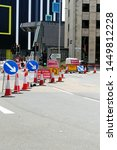 Small photo of Plymouth England July 2019. Road works with temporary traffic lights, red and white cones, blue and white pointing arrows and a surfeit of yellow and red ground level directional/instructional signs