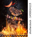 Small photo of Tasty beef steaks and skewers flying above cast iron grate with fire flames. Freeze motion barbecue concept.