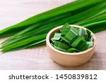 Small photo of Sliced pandan leaf in a bowl on wooden background, pandan leaf used to enhance the flavoring and color in Asia food and dessert