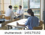 Stock photo male and female doctors communicating with nurse in foreground on work break in cafeteria 145175152