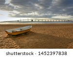 A lone rowboat sets on an empty ...