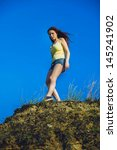 Small photo of acrophobia punk woman hippie suicide tall stands on top of a rock cliff edge and is fearful horror