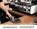 Small photo of Barista holding portafilter with milled coffee on tamp mat at bar counter, closeup. Space for text