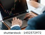 businessman or broker looking at computer laptop analysing about stock market invest trading stocks graph analysis candle line in office room. - stock photo