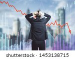 Small photo of Back view of stressed young businessman looking at downward red arrow on blurry city background. Decrease, investment and economy concept. Multiexposure