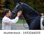 man kisses horse. girl riding a horse in park in Autumn near lake in the mountains. horseman and horsewoman. jockey teach to ride. equestrian sport concept. training to ride on horse. vacation on farm