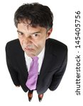 Small photo of Fun high angle full length portrait oaf a nasty businessman with an attitude sneering at the camera and looking up under his eyebrows isolated on white