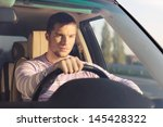 handsome young man driving a... | Shutterstock . vector #145428322