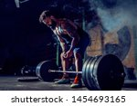 Small photo of Muscular fitness man preparing to deadlift a barbell in modern fitness center. Functional training. Snatch exercise