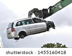 Small photo of Car in a scrap yard being lifted by a mechanical grabber crane to be scrapped