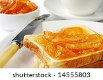 Toast with home-made orange marmalade, served with a cup of tea. - stock photo