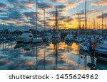 The marina yacht harbor of Oostende city, Ostend in English, at sunset with the city hall in the background, West Flanders, Belgium.