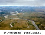 Aerial view of arctic tundra. Landscape with a winding river among the tundra and hills. Endless expanses of the Arctic. Travel to the extreme north. Chegitun River, Chukotka, Siberia, Far East Russia