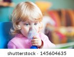 Small photo of Baby girl with asthma problems making inhalation with mask on her face