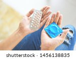 Small photo of Woman holding contraception pills and condom in hand / Birth control contraceptive means prevent pregnancy or sexually transmitted disease
