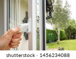 Small photo of Cambridgeshire, UK - Circa July 2019: Person seen opening in a newly installed double glazed window on a house annex. Multiple locks can be seen on the window frame, seen adjacent to a large garden.
