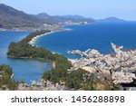 Hiryukan (The flying dragon view) of Amanohashidate, Kyoto, Japan, with full blossom cherry under a blue sunny sky. A pine covered sandbar spans the mouth of Miyazu Bay. Japan