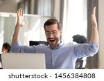 Small photo of Excited male employee look at screen scream with happiness witness sales rising or project success, happy man worker gesture yes winning lottery online, hit jackpot triumph in web game