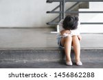 Small photo of Asian child touchy or kid girl sleeping and angry cry with sad or have problems and bend down the head lonely to wait for the parents on city street at nursery or kindergarten and pre school