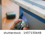 Small photo of Furniture cutting oscillating multi function power tool on kitchen cabinets framing