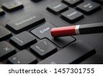 """Small photo of Pressing the """"enter"""" key on a black keyboard with a pencil"""