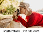 Stock photo gorgeous young blonde in red sweater and light hat kisses with love her labrador in autumn park 1457317025