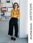 Small photo of Studious young businesswoman wearing heavy rimmed glasses standing leaning against a wall in the office with folded arms and a thoughtful expression