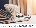 An Open Book With Glasses On A...