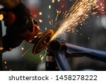 Small photo of Worker cutting, grinding and polishing motorcycle metal part with sparks indoor workshop, close-up.