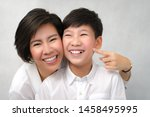 Small photo of A happy face of asian smart looking preteen boy and mom laughing together. Deciduous teeth, Milk teeth, Healthy and strong, Dental oral care, Bonding, Mother and son, Studio portrait white background.