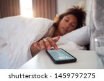 woman waking up in bed reaches... | Shutterstock . vector #1459797275