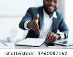 Small photo of Partnership concept. Smiling young African American businessman extending hand to shake.