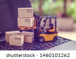 Small photo of Logistics, supply chain and delivery service concept : Fork-lift truck moves a pallet with box carton. Boxes on a laptop computer, depicts wide spread of products around globe in ecommerce booming era