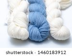 Small photo of Three skeins of yarn on a white background. Two cream/eggshell colored yarn skeins with a light blue skein in the middle.