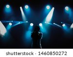 Small photo of Cool young rap singer with microphone on bright backlit stage in bright blue lights.Hip hop star performing solo set on scene in music hall.Popular rapper sings a song on rock festival in nightclub