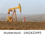 Yellow pumpjack -overground drive of a piston pump- lifting oil from a well in the Tazhong Oil Field of the Taklamakan Desert near the Taqie Hiighway-branch of the Tarim Desert Highway. Xinjiang-China - stock photo