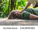 Small photo of Unconscious fainted girl having pulse checked by an old woman – Teenager lying on the ground while her pulse is verified by an elder citizen on teen's carotid artery