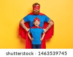 Small photo of Photo of confident ginger father and daughter keep hands on waists, pretend being superhero and defend people, wear special costumes, isolated on yellow background. Family team ready to work