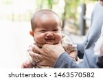 Small photo of Close up of asian father is holding his baby neck to belch burping after breastfeeding. Father spending time with his daughter outdoor. Maternity and baby care.