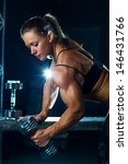 Young woman bodybuilder with dumbbell. - stock photo