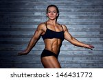 Woman bodybuilder on wall background. - stock photo