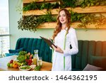 Portrait of a young woman nutritionist in medical gown standing with clipboard and tape measure in the office with healthy food on the background. Weight loss and right nutrition concept
