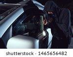 thief intruding car with flashlight and crowbar at night - stock photo