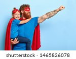 Small photo of Glad family being heroic leaders, wear superhero costumes, have determination to achieve goal and challenging obstacles, caring father holds little girl, ready for flight, isolated on blue background