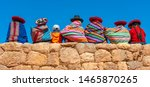 Panoramic photograph of Quechua indigenous women in traditional clothing with a boy sitting on an ancient Inca wall in Chinchero, Cusco Province, Peru.