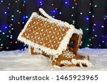 Small photo of The crashed hand-made eatable gingerbread house, snow decoration, garland background illumination