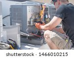 Small photo of Hvac repair technician using a volt meter to test components on an air conditioner condenser.
