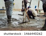 Group of workers with trowel and wooden tools build the concrete floor at the construction site. - stock photo